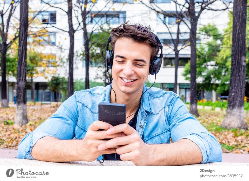 Young man looking at smartphone with headphone on his head headphones sitting earphones happy listening smiling young mobile guy technology person music