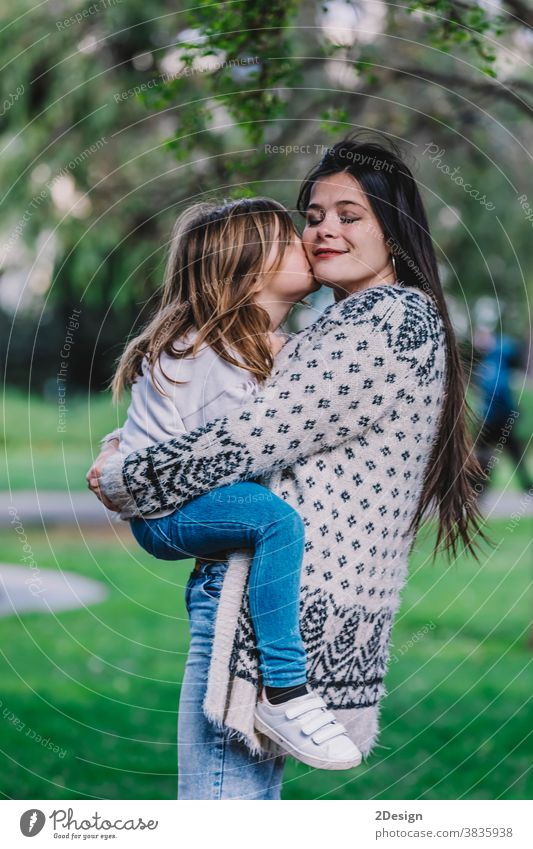 Little cute child baby girl kiss on cheek and hug, embrace with happy pretty woman in green park. Mother, little kid daughter. Mother's Day, love family, parenthood, childhood