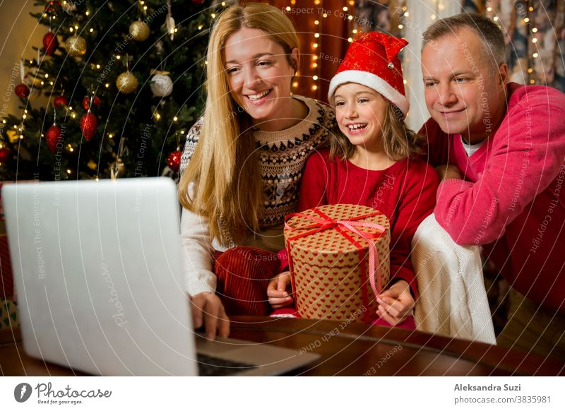 A happy couple with a child is celebrating Christmas with their friends on video call using webcam. Family greeting their relatives on Christmas eve online. New normal