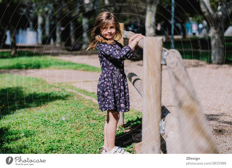 Portrait of a pretty smiling little child girl standing in park outdoors. young adorable childhood cheerful person toddler cute happy boy beautiful portrait