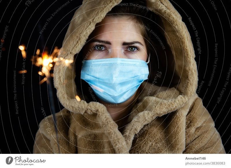 Happy new year, portrait of a young woman wearing medical mask and holding sparklers light in the dark for Covid-19, Coronavirus and New year concept