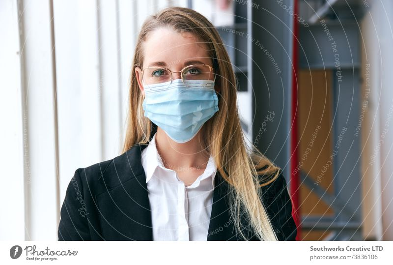 Portrait Of Young Businesswoman Wearing Mask Standing In Modern Office During Health Pandemic business businesswoman face mask face covering wearing ppe working