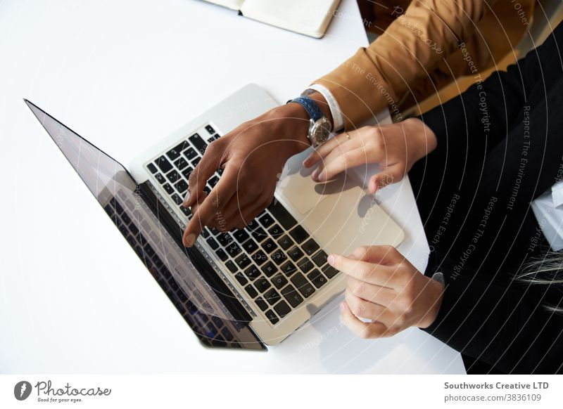 Close Up Of Businessman And Businesswoman At Hot Desk Meeting And Working On Laptop In Modern Office business businessman businesswoman meeting office hot desk
