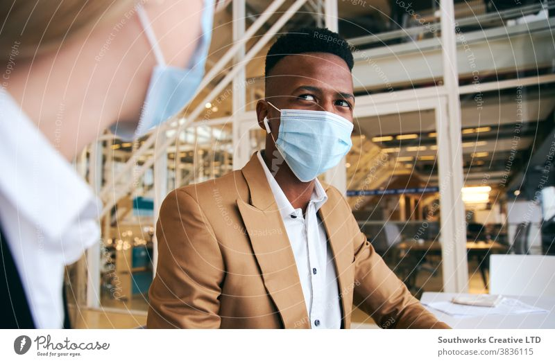 Business Couple Wearing Masks Meeting At Hot Desk In Modern Office During Health Pandemic business businessman businesswoman face mask face covering wearing