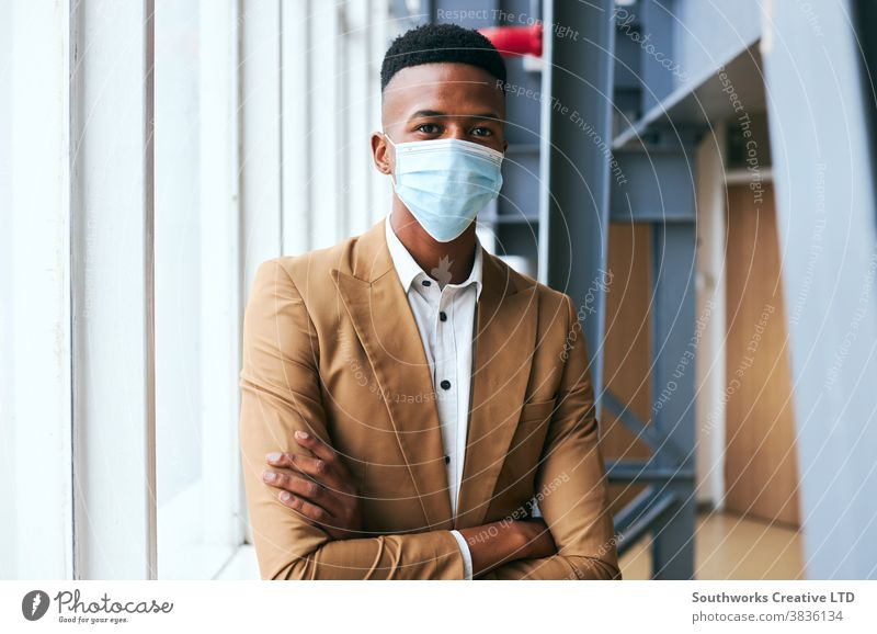Portrait Of Young Businessman Wearing Mask Standing In Modern Office During Health Pandemic business businessman face mask face covering wearing ppe working