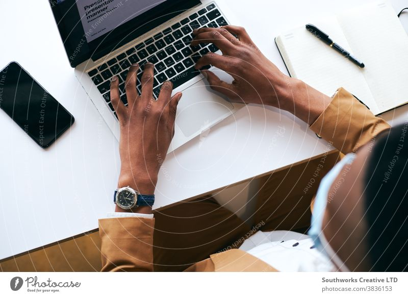 Overhead Shot Of Businessman Wearing Mask Working On Laptop At Hot Desk In Office In Health Pandemic business businessman face mask face covering wearing ppe