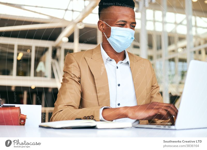 Young Businessman Wearing Mask Working On Laptop At Hot Desk In Office During Health Pandemic business businessman face mask face covering wearing ppe working