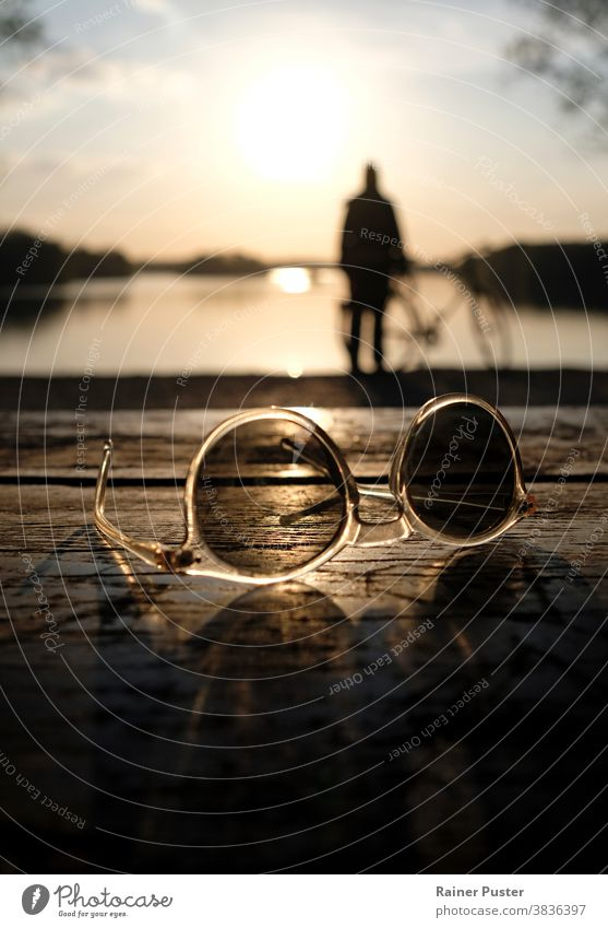A calm sunset at a lake with a pair of sunglasses in the foreground background calmness closeup dawn design dusk evening idyllic light nightfall object