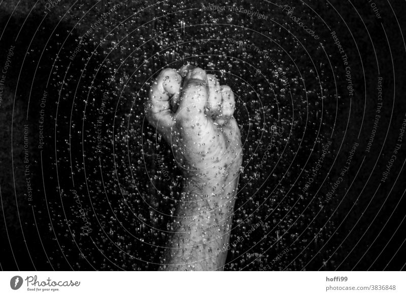Close-up of a clenched fist surrounded by drops of water Fist raised fist raindrops Fight Force Protest Anger Frustration resistance tropics Drops of water