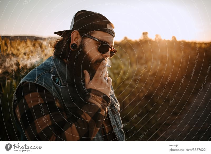 young man with beard, sunglasses and cap smokes teen Sunset out Field Hip & trendy Hipster Man Smoking Cigarette Sunglasses Headwear Unhealthy Lifestyle Cool