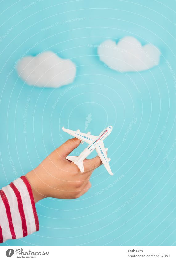 child hands holding a toy airplane over clouds. Travel concept travelling voyage explore aviator travel agency travel concept kid blue destination traveler