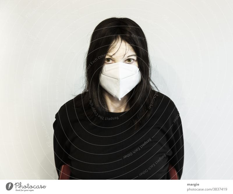 A frightened and frightened woman with a mouth guard, mask Woman Young woman Mask Mask obligation corona corona crisis corona virus Black Black-haired scared