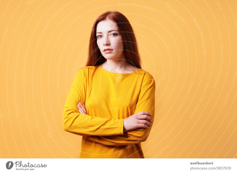 colorful studio portrait of confident young woman with her arms folded adult person people yellow orange background female beautiful attractive girl pretty