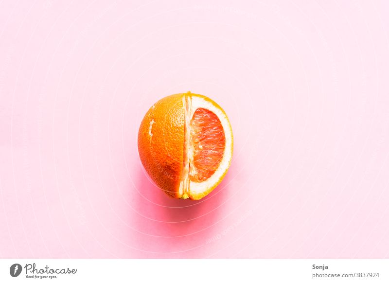 A sliced grapefruit on a pink background. Grapefruit Raw Citrus fruits Nutrition Colour photo Healthy Eating Organic produce Vegetarian diet Vitamin Vitamin C