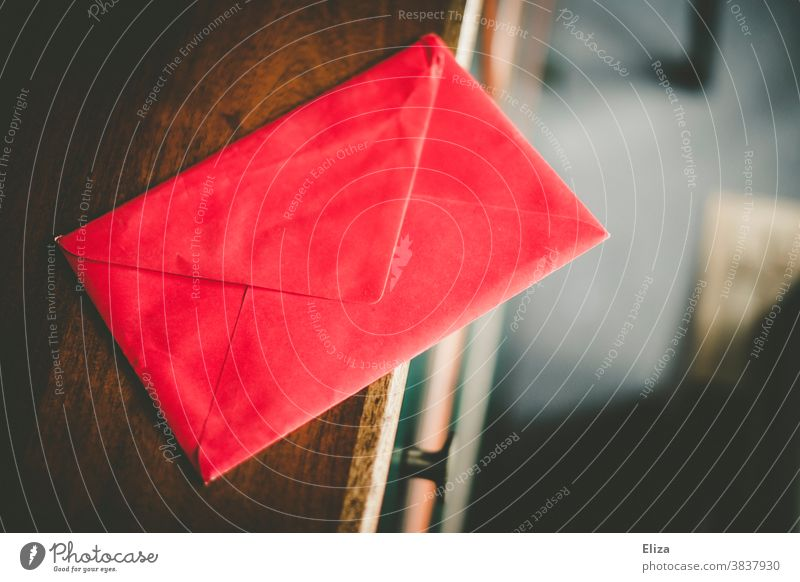 A sealed red envelope on a chest of drawers Envelope (Mail) Red Letter (Mail) message Love letter Dark Write locked