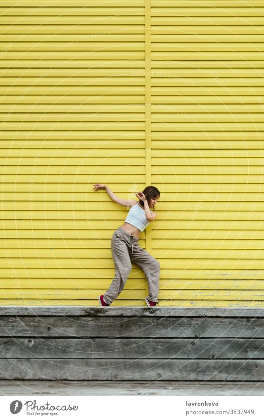 Young adult female in white top and grey pants dancing in front of bright yellow wall dancer choreographer hiphop outdoors girl stylish urban movement sport