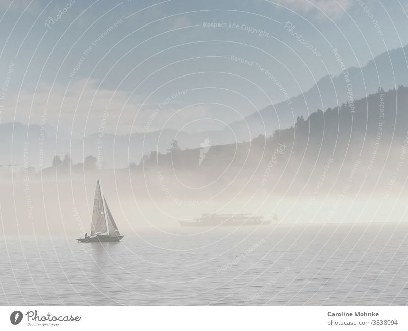 A rare fog atmosphere on Lake Lucerne: a sailing ship in the foreground, a blanket of fog on the lake in the background. Another ship can be seen in it and in the background the Alps.