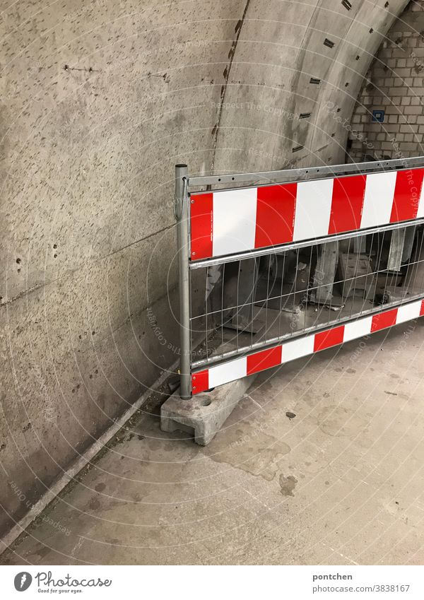 A red and white striped barrier in front of a concrete wall.  Safety, Warning, Prohibition cordon Grating Reddish white interdiction Passage Underground Barrier