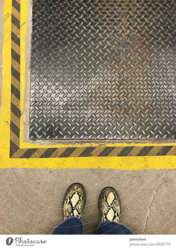 Pattern mix. Snakeskin shoes in front of striped floor marking and manhole cover Manhole cover Footwear Stripe Covers (Construction) Shaft Protection iron cover