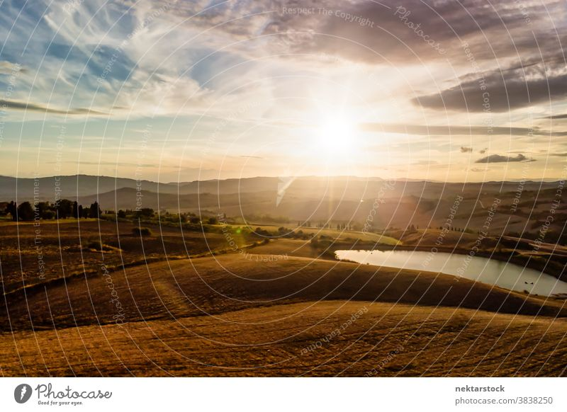 Italian Landscape Panorama with Silhouetted Mountains and Cloudscape Tuscany Italy landscape cloudscape panorama agriculture field lake sun sunrise rural