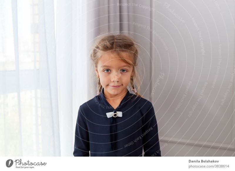 Close up shot of beautiful caucasian little girl with pigtails, looking at camera with charming smile, posing against light window and painted wall. Concept of happy childhood