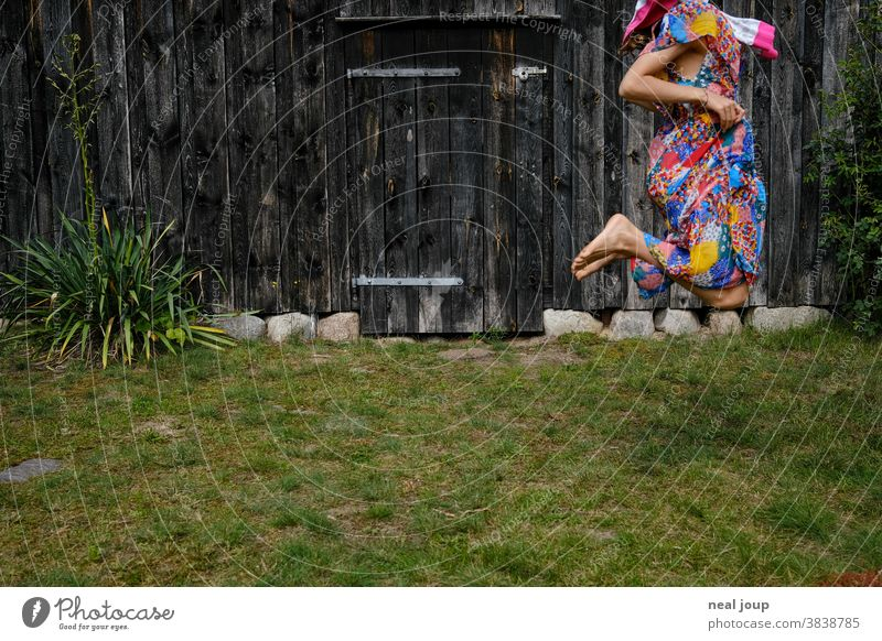 Jumping child in front of the wall of an old barn Child Hop Playing Happiness fun game Dress up variegated Grass Lawn Garden Summer Green broached Girl Joy