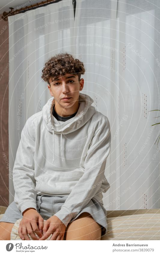 Attractive young man with curly hair wearing white sweatshirt posing on white curtains background cheerful casual smile male adult handsome happy attractive