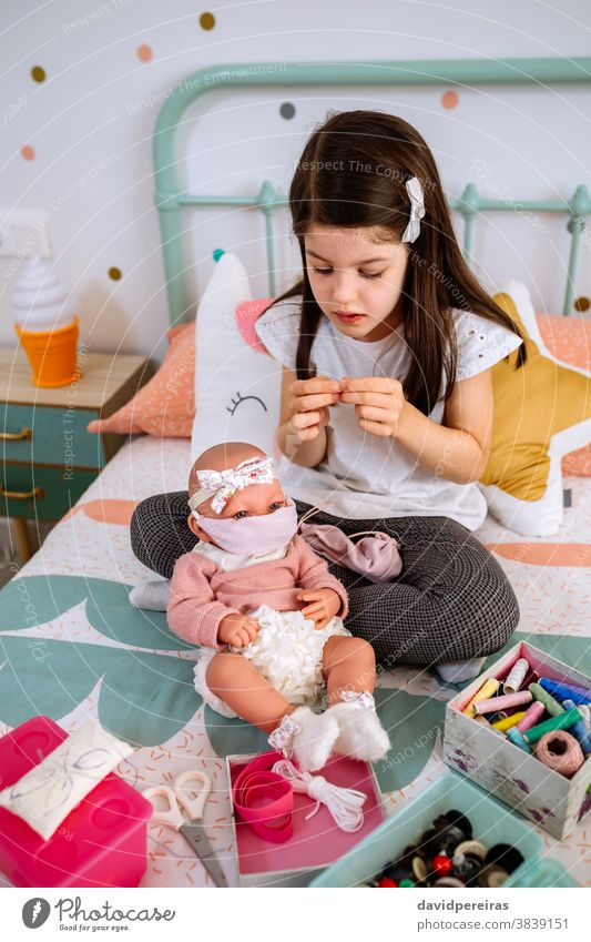 Girl sewing face masks for herself and her baby doll girl playing thread coronavirus protection sewing box health concept needle covid generation protective