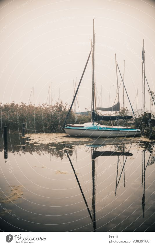 Small sailing boat lies in the fog at the landing stage Sailboat Dinghy Lake Water Harbour Sailing Sailing trip jetty Watercraft Fog foggy holidays vacation