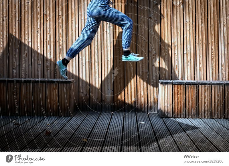 Big jumps Jump Wood benches wooden benches Wooden wall sneakers Girl Child Shadow Pants lively Funny youthful Dynamic elan Happiness Infancy fun Playing