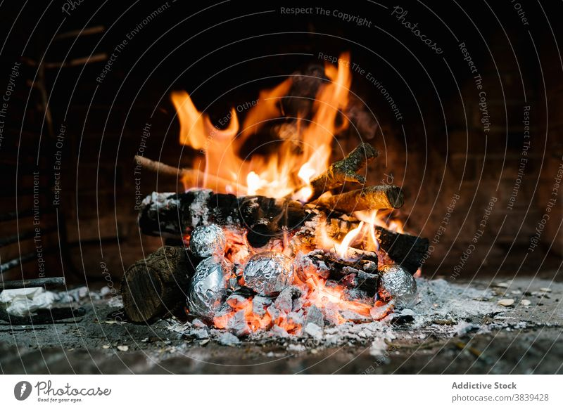 Fire burning in fireplace at home flame chimney potato baked foil aluminium delicious prepare rustic house heat hot warm tradition cozy light food blaze rural