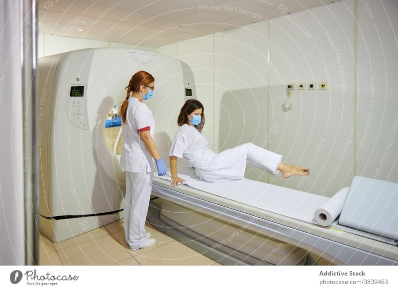 Radiologist and patient on tomography equipment in clinic radiologist diagnostic health care uniform mask professional women together lying couch scan machine