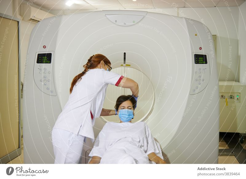 Unrecognizable radiologist and patient on tomography equipment in clinic diagnostic health care uniform mask professional women together lying couch scan