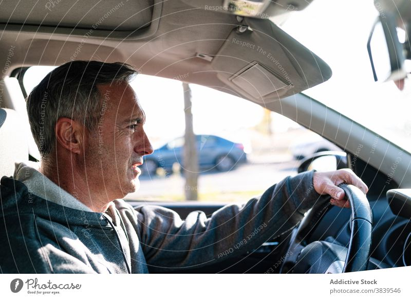 Senior retired man driving car steering wheel pilot traffic healthy vision reflexes senior 60 journey person horizontal one person happy old car insurance