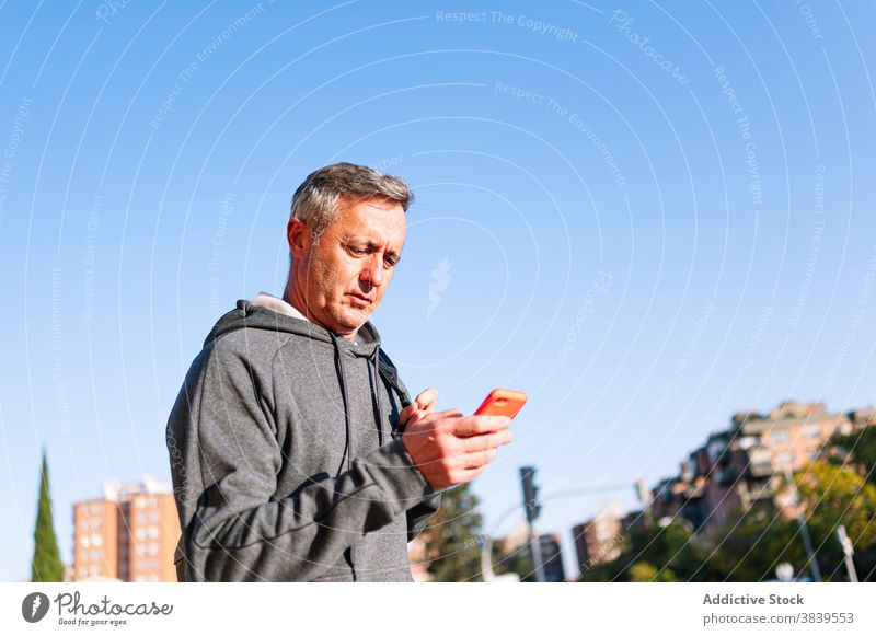 Senior retired man with sportswear and smart phone walking down the street 60 rest rythm health care fitness training cardiac old neck rate caucasian check