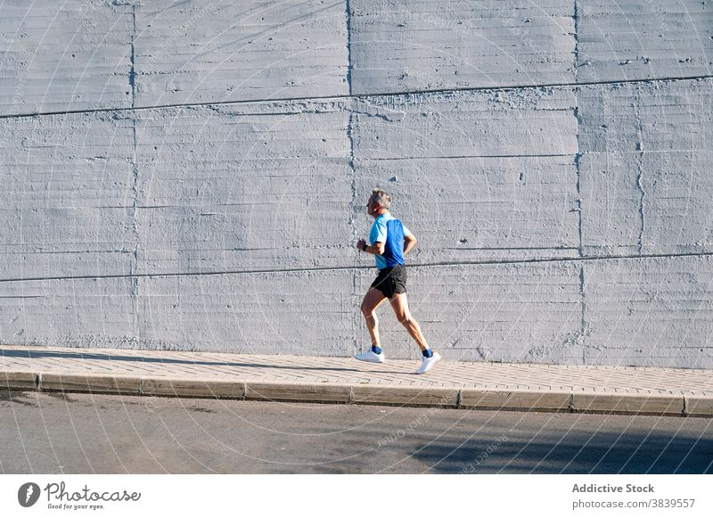 Senior retired man runs down the street 58 rest rythm health care fitness high-blood-pressure training cardiac old neck rate caucasian check sport old man time