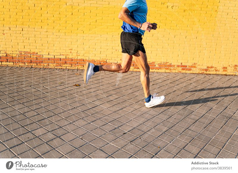 Unrecognizable senior retired man running through the city on yellow background 60 58 rest rythm health care fitness high-blood-pressure training cardiac old