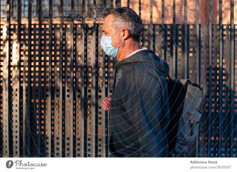 Senior retired man with face mask and sportswear walking down the street 58 rest rythm health care fitness high-blood-pressure training cardiac old neck rate