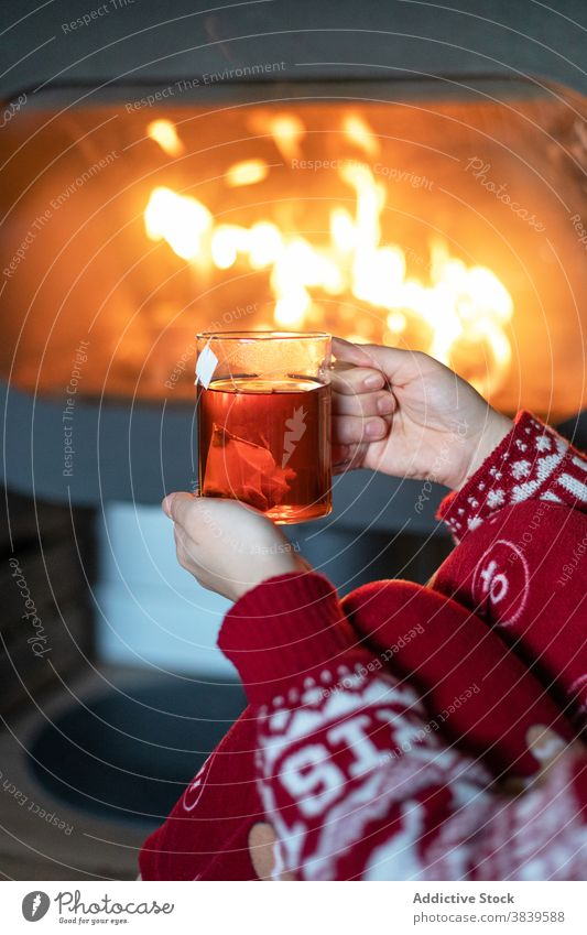 Crop woman with cup of tea near fireplace christmas cozy warm atmosphere chimney holiday night female red xmas new year sweater relax beverage winter drink sit
