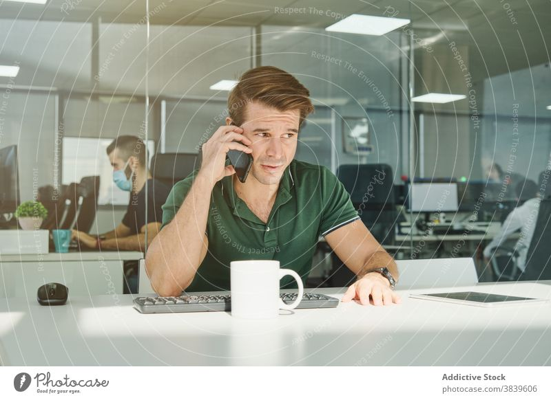 Male office worker talking on smartphone at table man discuss project smile workplace employee male cellphone busy business professional conversation modern sit