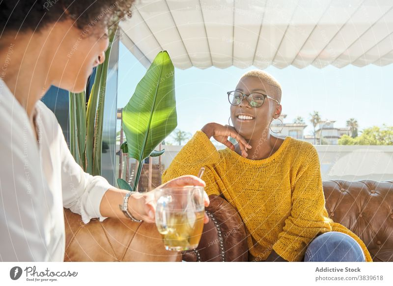 Cheerful black women telling jokes and laughing friendship having fun best friend humor positive terrace summer ethnic african american talk together happy