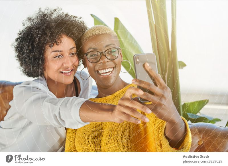 Delighted black lesbian couple taking selfie on smartphone women love lgbt self portrait hug equal ethnic african american mobile smile armchair embrace device