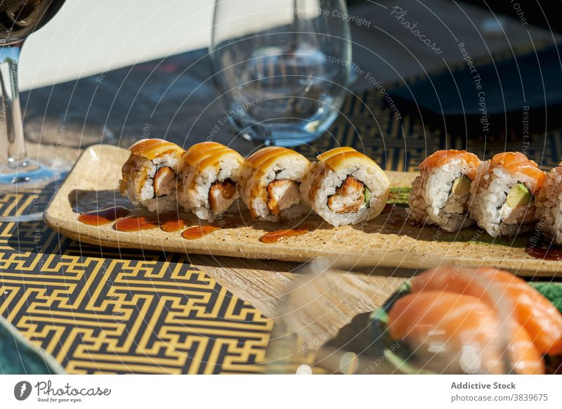 Table with sushi in restaurant roll woman asian food cafe eat various wine assorted set glass ethnic black african american table dish tasty delicious meal