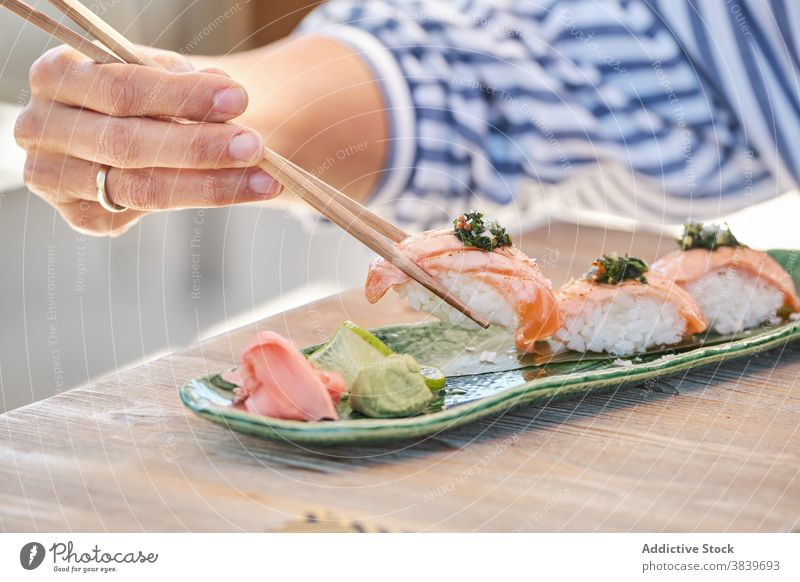 Anonymous person eating tasty sushi Nigiri on plate in cafe nigiri rice salmon asian food restaurant seafood oriental tradition fish delicious gourmet dish meal