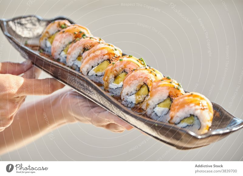 Various sushi and rolls in plates on table set assorted asian food seafood california restaurant meal delicious dish cuisine tasty fresh serve oriental gourmet