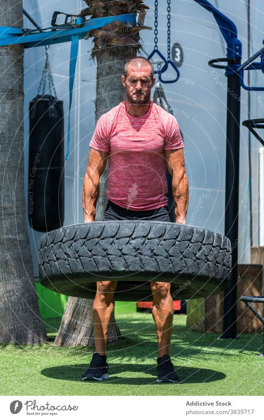 Strong sportsman doing exercises with heavy tire workout functional strong tyre lift athlete male muscular power healthy energy determine fitness active