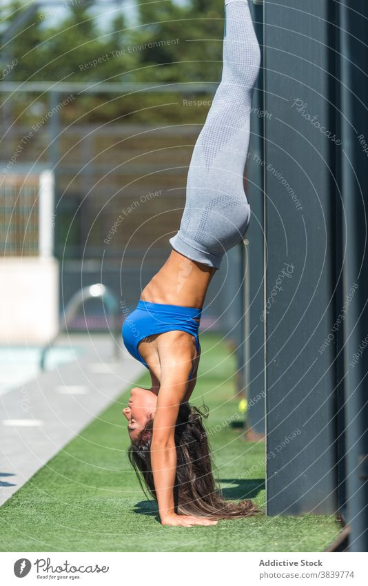Slim woman doing handstand during training wall sportswoman acrobatic summer workout balance fit fitness female sportswear wellness healthy exercise flexible