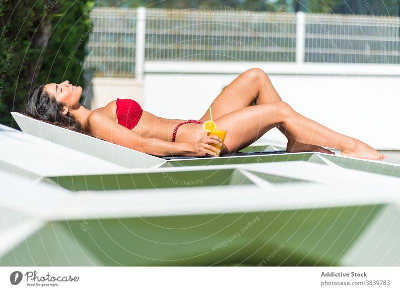 Carefree woman in bikini relaxing at poolside sunbath suntan deckchair summer vacation cocktail female fresh juice sunny weekend lady lying red resort swimwear