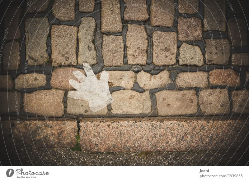 A disposable plastic glove lies on the cobblestone pavement disposable glove throwaway society Cobblestones Environmental pollution Trash Polluter