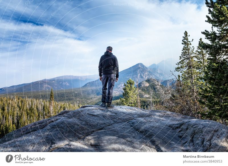 Man standing on a summit in the Rocky Mountain National Park and watching the smoke from the wildfires coming in the valley man tourist hiker caucasina
